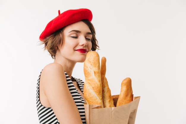Portrait of a pretty woman wearing beret smelling