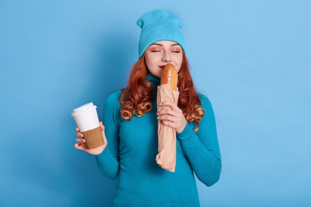 Portrait of pretty woman wearing blue attire smelling fresh long loaf and holding coffee to go,
