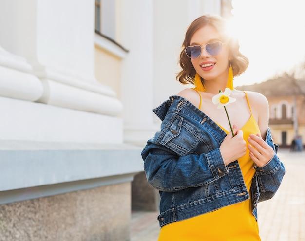 Ritratto di bella donna che indossa occhiali da sole a cuore tenendo il fiore contro il sole, soleggiata giornata estiva, abbigliamento elegante, tendenza della moda, giacca di jeans blu, vestito giallo, orecchini boho hipster eleganti
