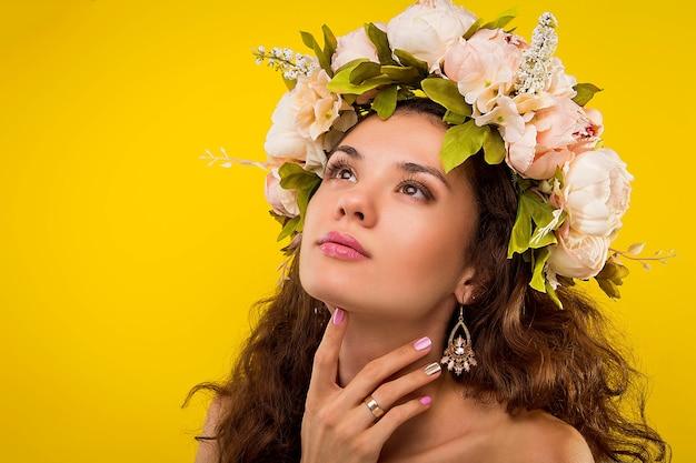 Portrait of a pretty woman wearing a wreath on yellow wall