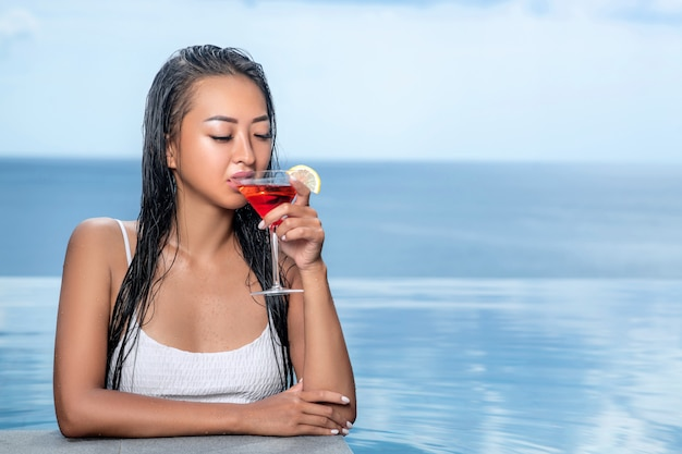 Portrait of  pretty woman in a white top who drinks of cosmopolitan cocktail.  beautiful sea view on blurry background. infinity pool  on the blurred backgrouns