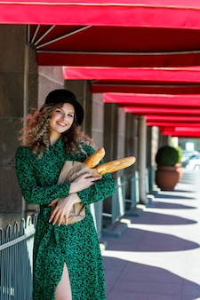 Portrait pretty woman with baguette in hands on street. woman dressed in french style