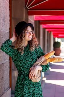 路上で手でバゲットを持つ肖像画のきれいな女性。フレンチ スタイルの服を着た女の子は、感情を表します。晴れの日