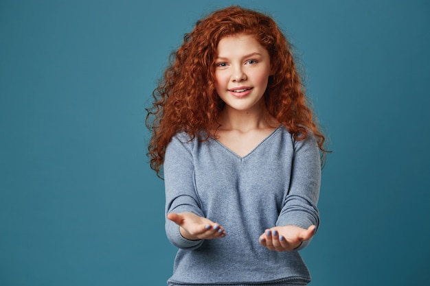Portrait of pretty woman with wavy red hair and freckles in grey shirt with happy and relaxed expression.