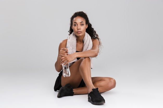 Portrait of a pretty young african sportswoman resting after training isolated over grey wall, drinking water