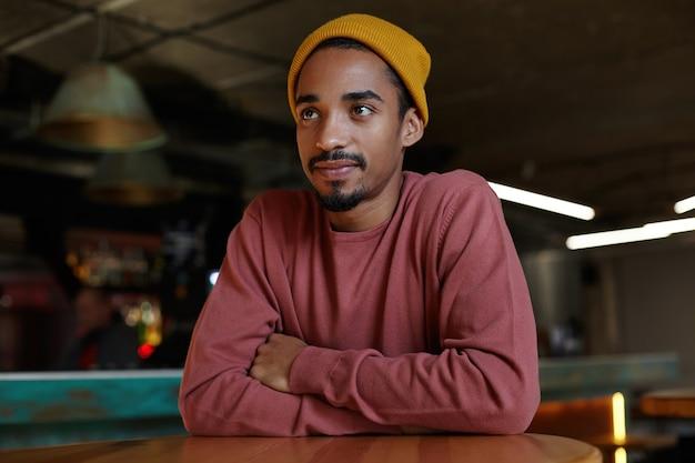 Ritratto di giovane maschio barbuto dalla pelle scura con affascinanti occhi marroni seduto al tavolo e mani pieganti su di esso, guardando da parte con viso calmo e pensando ai piani per la sera