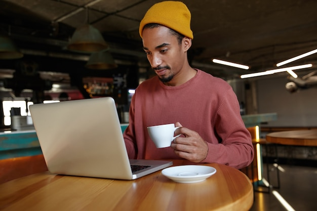 Portrait of pretty young bearded male freelancer with dark skin sitting at table with laptop and holding cup of tea in raised hand, typing letter to clients with keyboard, dressed in casual clothes