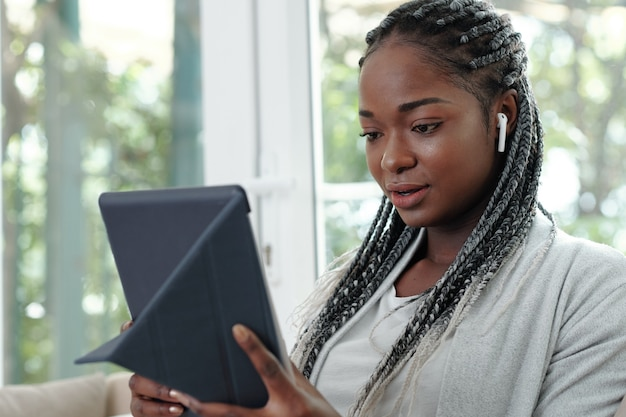 Portrait of pretty young black woman with braided hair wearing earbuds and videocalling her friend of family member