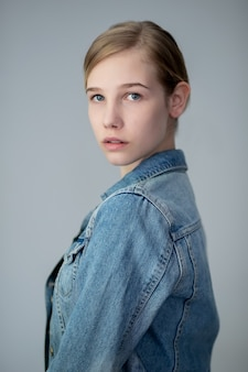 Portrait of a pretty young blond girl in a denim jacket with her arms crossed isolated against a light grey background