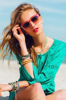 Portrait of pretty young blonde beautiful woman in cool sunglasses posing on the sunny tropical beach