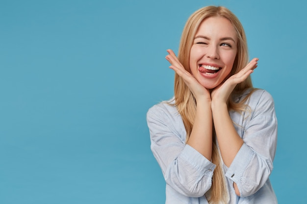 Portrait of pretty young blonde lady with long hair keeping head on raised hands, making faces, looking aside joyfully with closed eye and showinng tongue