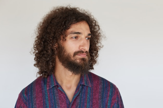 Portrait of pretty young brunette curly man with beard keeping lips folded while looking aside with calm face, wearing striped multi-colored shirt