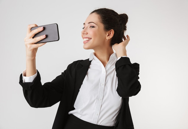 Portrait of a pretty young businesswoman taking a selfie