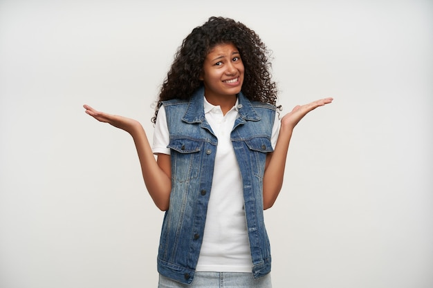 Ritratto di bella giovane donna bruna riccia dalla pelle scura che scrolla le spalle con le mani alzate e rughe sulla fronte, in piedi su bianco in giubbotto di jeans e camicia bianca