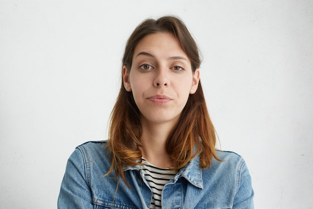 Portrait of pretty young female raising her eyebrow with wonder dressed in denim jacket isolated. suspicious woman frowning her face.