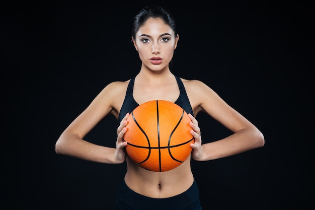Portrait of pretty young fitness woman holding and posing with basketball ball over black background