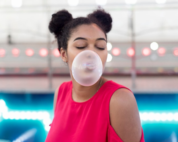 Portrait of pretty young girl blowing bubble gum