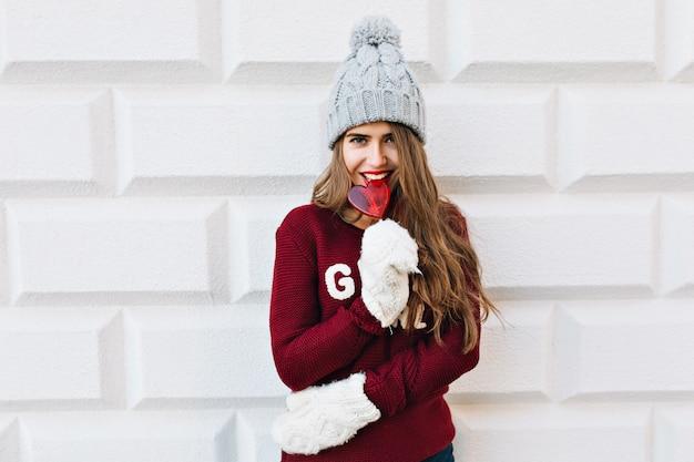 Ragazza abbastanza giovane del ritratto in maglione marsala e cappello lavorato a maglia sul muro grigio. indossa guanti bianchi, mangia lecca-lecca cuore rosso e sorride.