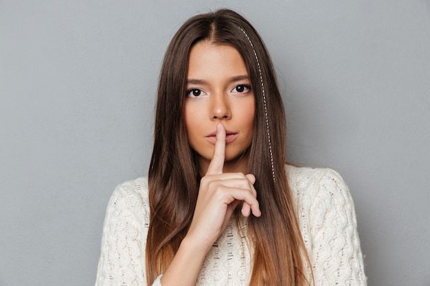 Portrait of a pretty young girl showing silence gesture