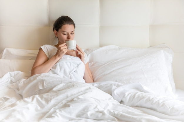 Portrait pretty young girl with coffee on bed in the morning