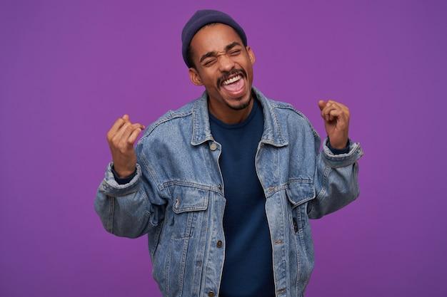 Ritratto di uomo castana barbuto dalla pelle scura abbastanza giovane felice che tiene gli occhi chiusi mentre solleva felicemente i suoi pugni, in piedi sopra il muro viola in abbigliamento casual