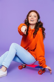 Portrait of a pretty young redheaded woman sitting on skateboard over violet, listening to music with headphones
