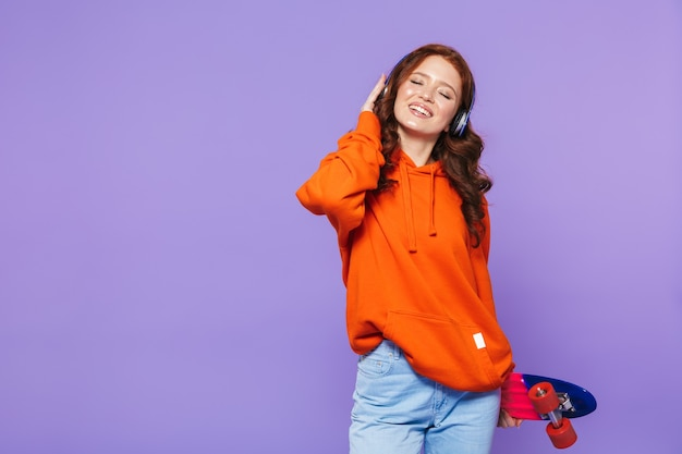 Portrait of a pretty young redheaded woman standing over violet, holding skateboard, listening to music with headphones