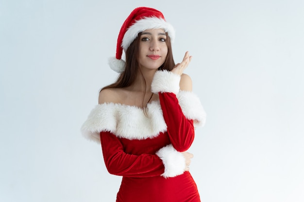 Portrait of pretty young smiling girl wearing santa claus dress