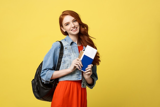 Portrait of pretty young student woman holding passport with tickets.