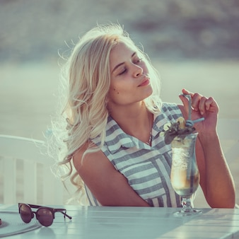 Portrait of pretty young woman in cafe on the beach drinking coctail, toned picture.