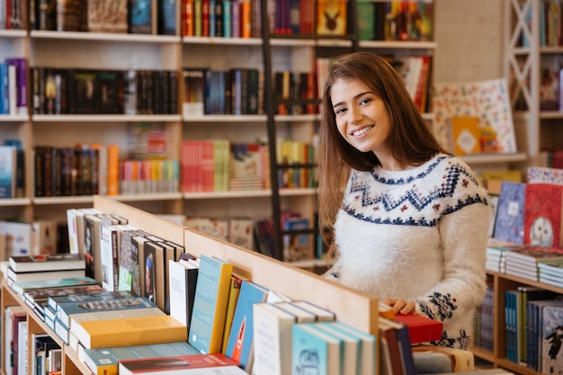 Portrait of a pretty young woman choosing books in library