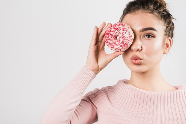 Portrait of pretty young woman covering her eyes with donuts