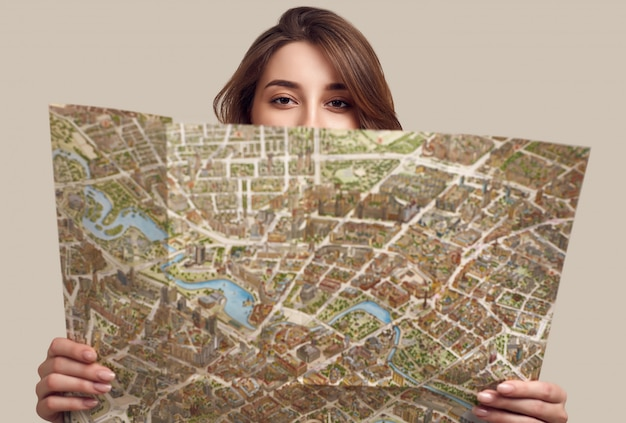 Portrait of pretty young woman holding map