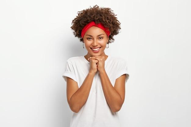 Ritratto di donna abbastanza giovane tiene le mani sotto il mento, sorride felicemente, vestito con un abbigliamento casual, gode di una bella giornata con la famiglia