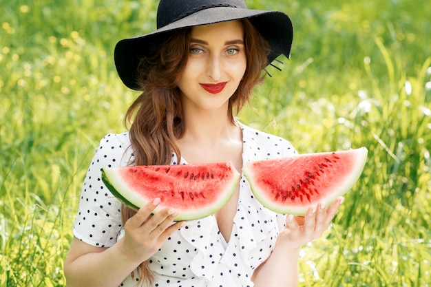 Portrait of pretty young woman is holding two slices of ripe watermelon.