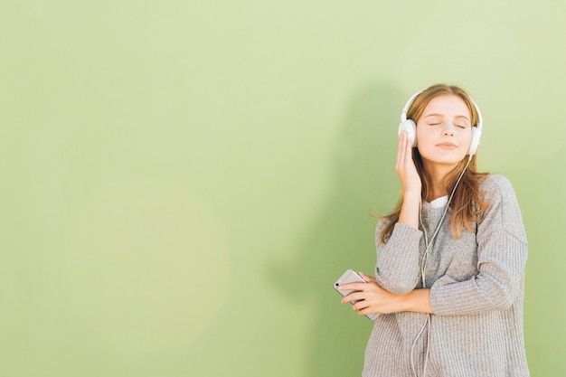 Portrait of a pretty young woman listening music on headphone through mobile phone against mint green backdrop
