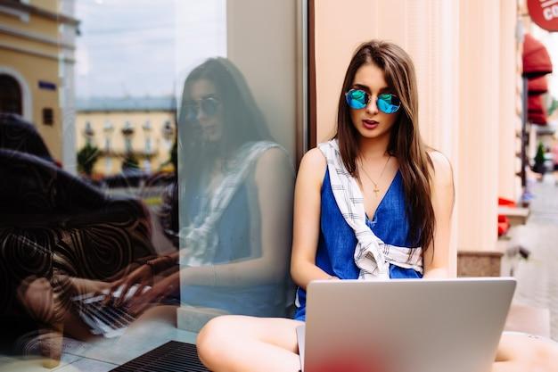 Ritratto di bella giovane donna seduta durante la giornata estiva durante l'utilizzo di laptop e auricolari wireless per la videochiamata