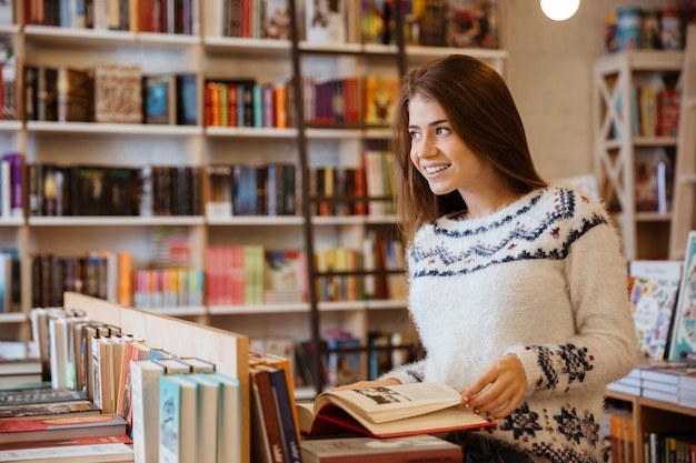 Portrait of a pretty young woman standing in a book store