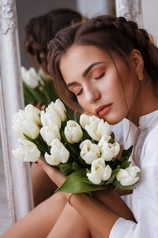 Portrait of pretty young woman in white dress looking at her reflection in mirror and holding spring flowers. beautiful natural girl posing against mirror with bouquet of tulips.  womens day