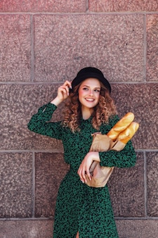 Portrait pretty young woman with baguette in hands on background texture of wall. girl dressed in french style show emotion with bread. female in stylish clothes holding fresh baguettes. copy space