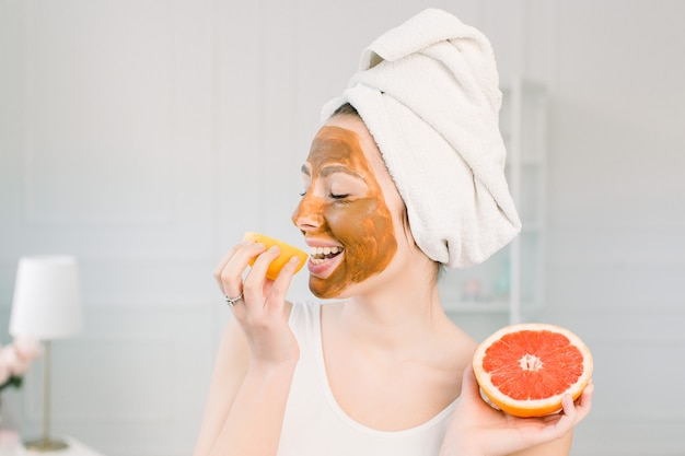 Portrait of pretty young woman with clay mask on her face holding slices of lemon and grapefruit, facial care