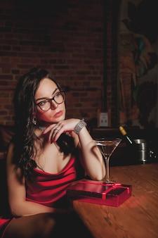 夜のレストランでギフトボックスと肖像画のかなり若い女性。贈り物のために悲しい女性。親密な雰囲気の中でバレンタインデーを祝うというコンセプト。あなたの最愛の人へのロマンチックなプレゼント。コピースペース