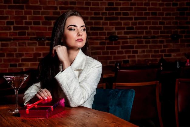 夜のレストランでギフトボックスと肖像画のかなり若い女性。女性の笑顔のオープニングギフト。親密な雰囲気の中でバレンタインデーを祝うというコンセプト。あなたの最愛の人へのロマンチックなプレゼント。コピースペース