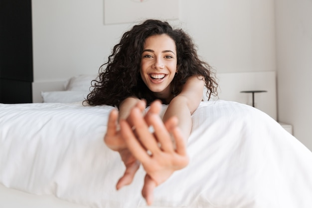 Portrait of prettyy european woman with long curly hair lying in bed with white linen in apartment, and stretching arms to you with smile