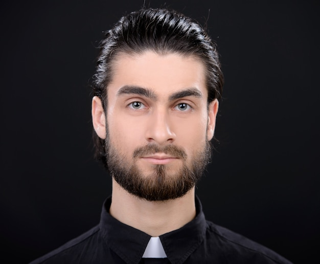 Portrait of priest standing isolated on black.