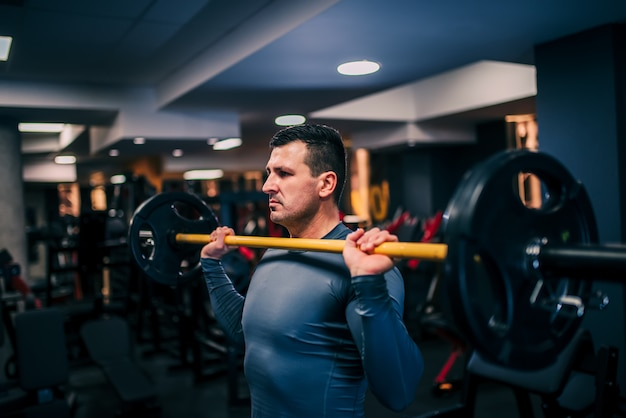 Portrait of professional bodybuilder working out with barbell at the gym, side view.