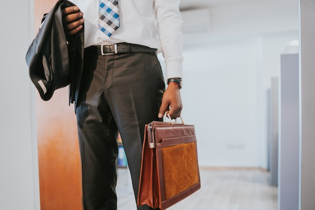 Portrait of professional businessman holding a briefcase while standing at modern office. business concept.
