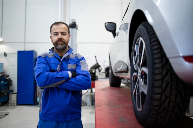 Portrait of professional car mechanic standing in vehicle workshop by an automobile.