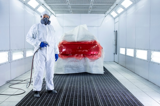Portrait of professional car painter holding painting gun and standing by automobile in the chamber.