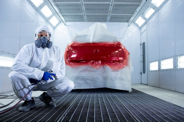 Portrait of professional car painter with protective clothing and mask holding painting gun and standing by automobile in the chamber.